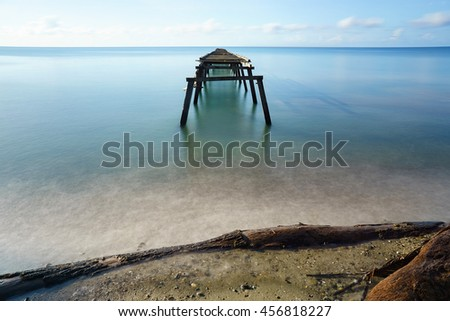 Broken old jetty at the middle of serene seascape create romantic and tranquil scene during day time. - stock photo