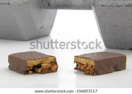 Broken protein bar with large dumbbell in the background. - stock photo