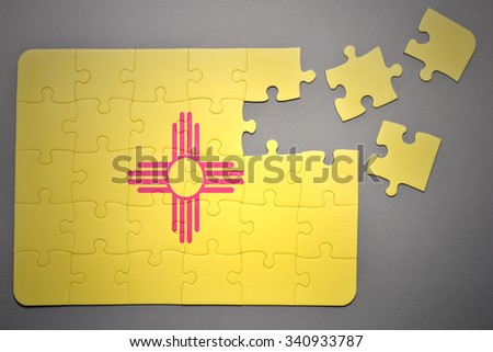 broken puzzle with the flag of new mexico state on a gray background - stock photo