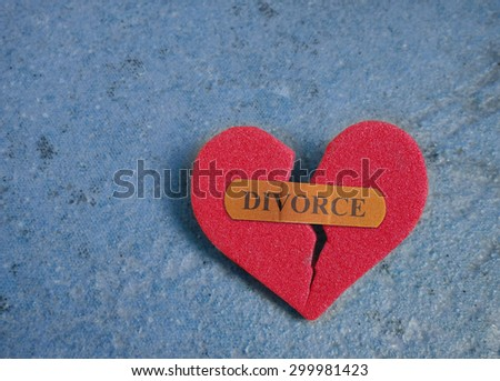 Broken red heart with a Divorce bandaid, on blue                                - stock photo