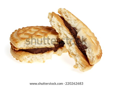 Broken sandwich biscuits with chocolate cream on a white background - stock photo