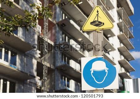 "Broken sign ""Hard hat area"" near under construction building on background - stock photo"