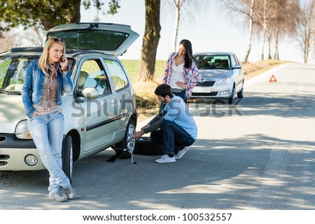 Broken wheel man changing tire help two female friends - stock photo