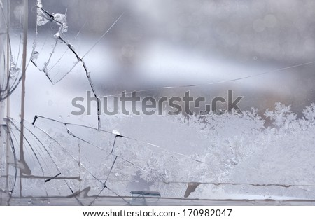 Broken window in the winter time with frost on the glass - stock photo