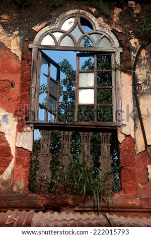 Broken window on an old red wall - stock photo