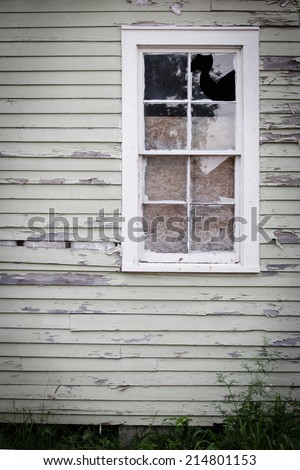 broken window on house with peeling paint - stock photo