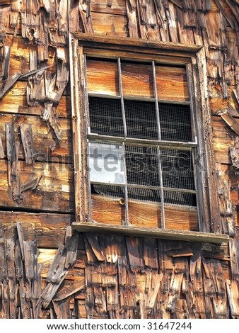 Broken window on side of weathered barn, with deteriorating shingles and chicken wire. - stock photo