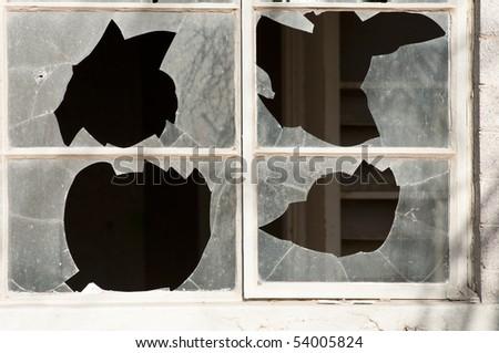 broken windows in an abandoned building that has been vandalized - stock photo