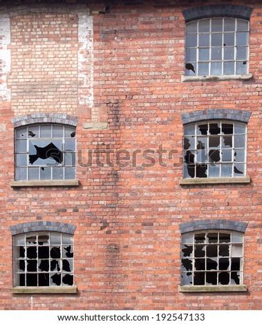 Broken windows in an old building - stock photo