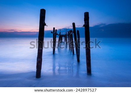 Broken wood bridge and waves crashing on sea - stock photo