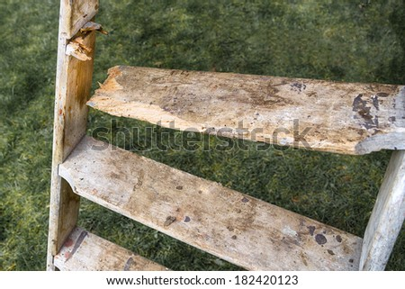 Broken wooden tread on a wood step ladder - stock photo