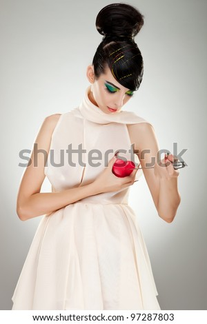 brokenhearted woman in fashion dress pointing a big kitchen knife at her heart - stock photo