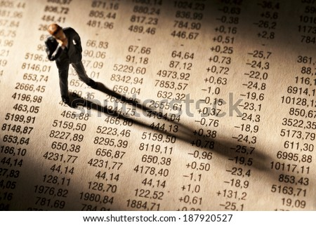 Broker stands on stock price chart, and casts a long shadow. - stock photo