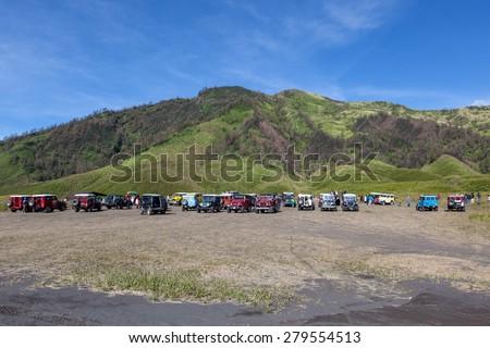 Bromo-Tengger-Semeru NP, JAVA/INDONESIA - April 17, 2015: Tourist jeeps in savanna of Tengger caldera near Bromo volcano at Java island in Indonesia. - stock photo