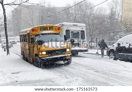 BRONX, NEW YORK - JANUARY 21: A school bus and other traffic during a 6 to 10 inch snow storm with teen temperatures along Ogden avenue and 162nd street.  Taken January  21,  2014 the Bronx, New York. - stock photo