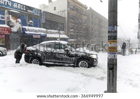 BRONX, NEW YORK - JANUARY 23: Man pushes stuck auto on Anderson Avenue street during Blizzard storm Jonas.  Taken January 23, 2016, in the Bronx,  New York. - stock photo