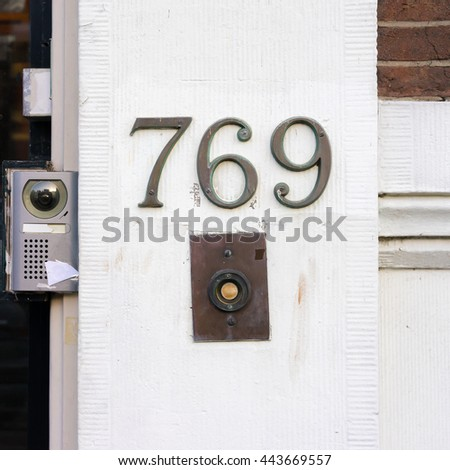 Bronze house number seven hundred and sixty nine above a doorbell, next to a door camera - stock photo
