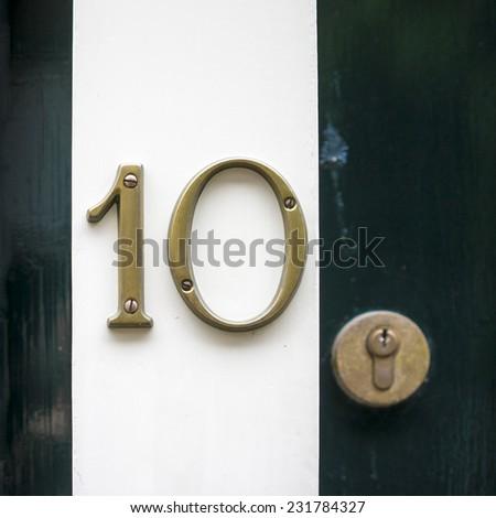 Bronze house number ten. Separate numerals on a doorpost - stock photo