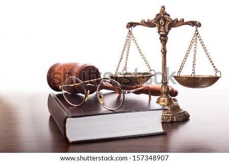 Bronze scales, judges gavel, book and glasses on the table - stock photo