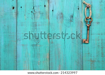 Bronze skeleton key hanging by rope on antique teal blue rustic wood door - stock photo