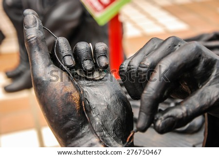 Bronze statue of human's hand with coins - stock photo