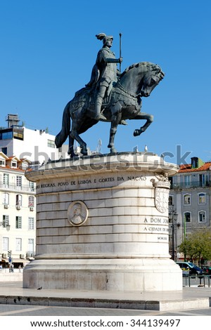 Bronze statue of King Joao I in Praca da Figuerira with a bird on statue's head in Lisbon, Portugal - stock photo