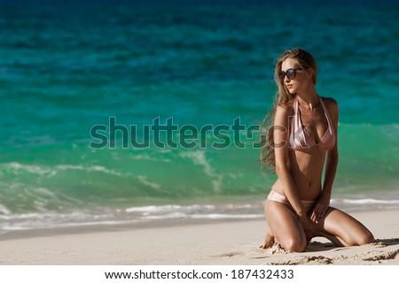 Bronze Tan Woman Sunbathing At Tropical Beach - stock photo
