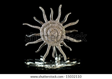 Brooch the sun on a black background - stock photo