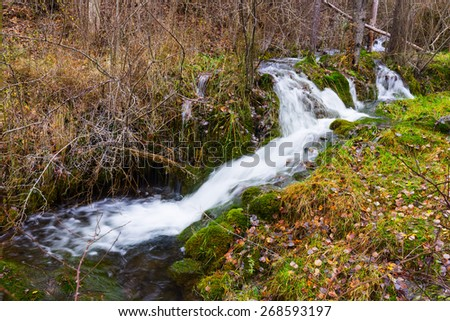 brook with moss stones at forest in autumn - stock photo