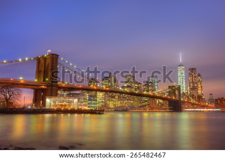Brooklyn bridge and New York City Manhattan downtown skyline at dusk with skyscrapers illuminated over East River panorama. Copy space. - stock photo