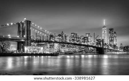Brooklyn bridge and New York City Manhattan downtown skyline at dusk with skyscrapers illuminated over East River panorama. Copy space. Black and white image. - stock photo