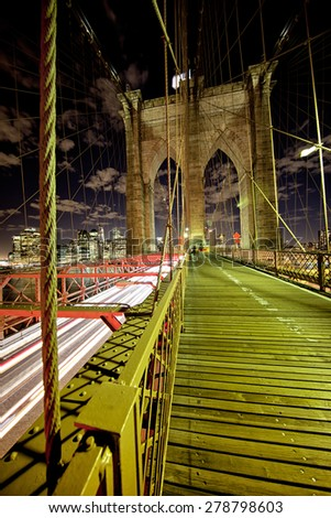 Brooklyn Bridge at night with speeding traffic - stock photo
