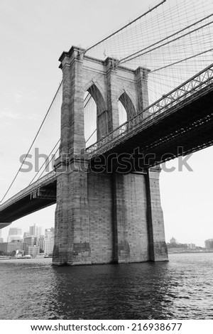 Brooklyn Bridge black and white over East River viewed from New York City Lower Manhattan waterfront. - stock photo