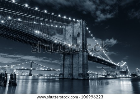 Brooklyn Bridge over East River at night in black and white in New York City Manhattan with lights and reflections. - stock photo