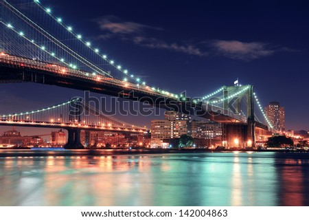 Brooklyn Bridge over East River at night in New York City Manhattan with lights and reflections. - stock photo