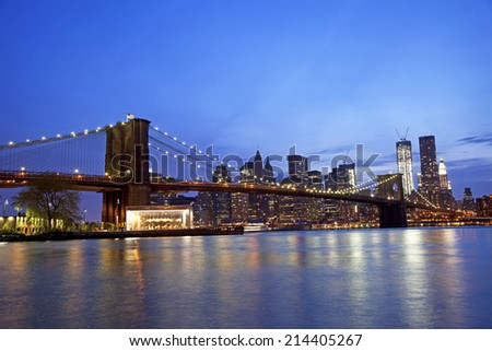 Brooklyn Bridge reflection over water during a sunset - stock photo