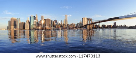 Brooklyn Bridge with lower Manhattan skyline panorama in the morning with cloud and river reflection over East River in New York City - stock photo