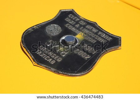 BROOKLYN, NEW YORK - JUNE 12, 2016: Vintage New York City taxi medallion in New York. Canary yellow in color, medallion taxis are able to pick up passengers anywhere in the five boroughs. - stock photo
