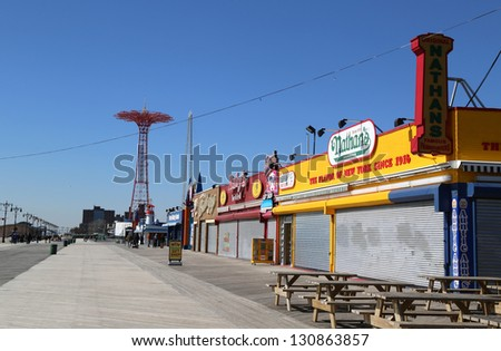 BROOKLYN, NEW YORK - MARCH 5: Coney Island Boardwalk with Parachute Jump in the background on March 5, 2013 at Coney Island, NY. The boardwalk, built in 1923, stretches for 2.51 miles. - stock photo