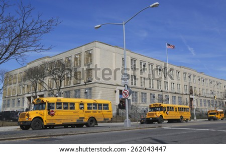 BROOKLYN, NEW YORK - MARCH 19, 2015: School buses in the front of public school in Brooklyn. New York City has the largest school transportation department in the country. - stock photo