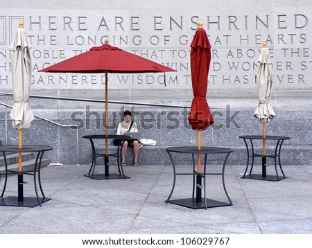 BROOKLYN, NEW YORK - MAY 29: An unidentified woman uses a computer outside the Brooklyn Public Library in Brooklyn, NY on May 29, 2009. It is the fifth largest public library system in the United States, including 58 branch libraries. - stock photo