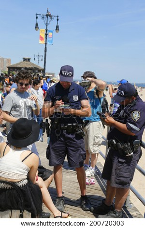 BROOKLYN, NY- JUNE 15:NYPD officers writing ticket for alcohol-related offense at Coney Island Boardwalk  in Brooklyn on June 15, 2014. The NYPD established in 1845, is the largest police force in USA - stock photo