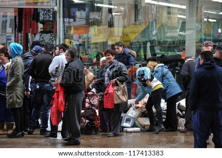 BROOKLYN, NY - NOVEMBER 01: Department store gives away to people wet merchandise at the Brighton Beach due to impact from Hurricane Sandy in Brooklyn, New York, U.S., on November 01, 2012. - stock photo