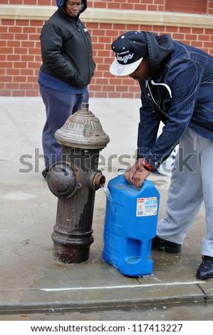 BROOKLYN, NY - NOVEMBER 01: People at the Seagate neighborhood feeling up water from fire hydrant  due to impact from Hurricane Sandy in Brooklyn, New York, U.S., on Thursday, November 01, 2012. - stock photo
