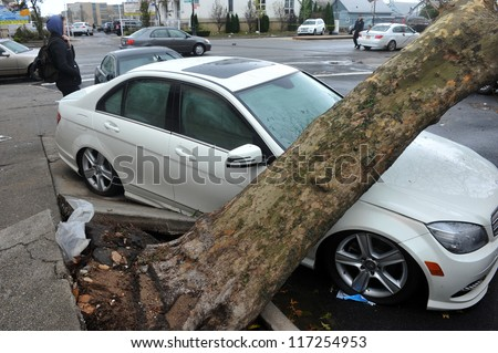 BROOKLYN, NY - OCTOBER 30: A fallen tree lies across a car n the Sheapsheadbay neighborhood due to flooding from Hurricane Sandy in Brooklyn, New York, U.S., on Tuesday, October 30, 2012. - stock photo
