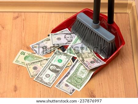 Broom sweeps dollars in the garbage scoop - stock photo