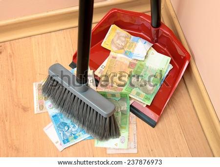 Broom sweeps the Ukrainian hryvnia in the garbage scoop - stock photo