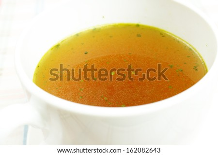 Broth, bouillon, clear soup in a large white bowl close-up. - stock photo
