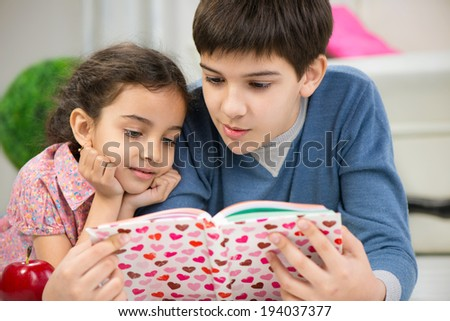 Brother and cute little sister reading book at home - stock photo