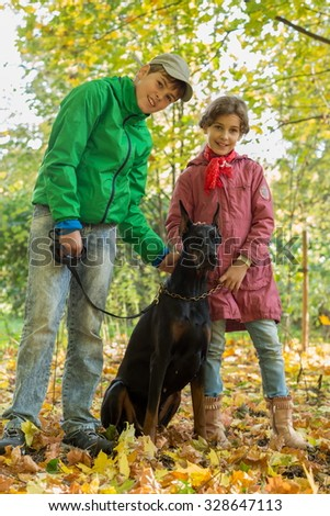 Brother and his sister are standing near the black dog in a forest. - stock photo